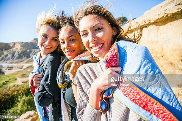 Women wrapped in blanket on rural hillside