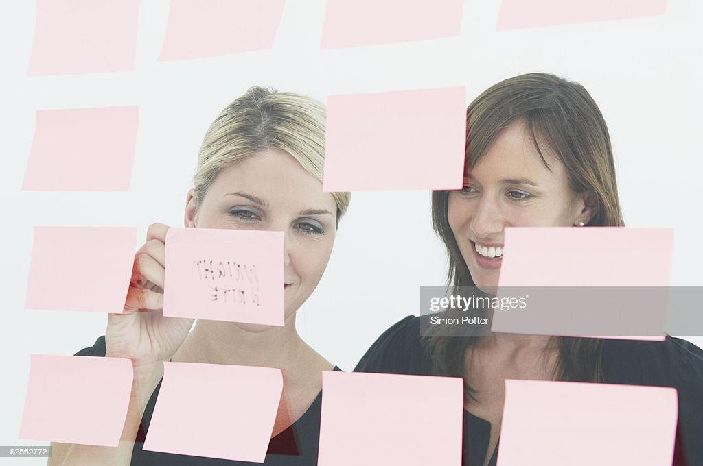 Women writing notes on glass wall : Stock Photo