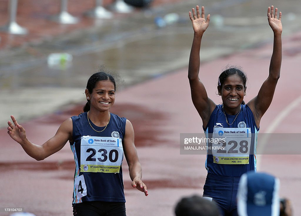 Women's 200 meters respective silver and bronze medal winners from India Asha Roy (R) and Dutee Chand wave to the crowd after their race on the fifth and the final day of the Asian Athletics Championship 2013 at the Chatrapati Shivaji Stadium in Pune on July 7, 2013. AFP PHOTO/Manjunath KIRAN