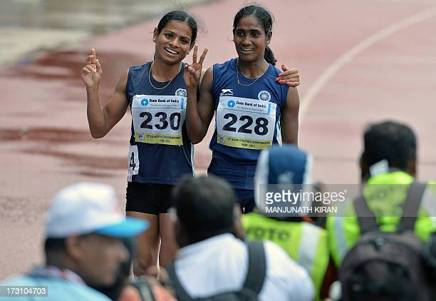 Women's 200 meters respective silver and bronze medal winners from India Asha Roy and Dutee Chand flash victory signs after their race on the fifth...