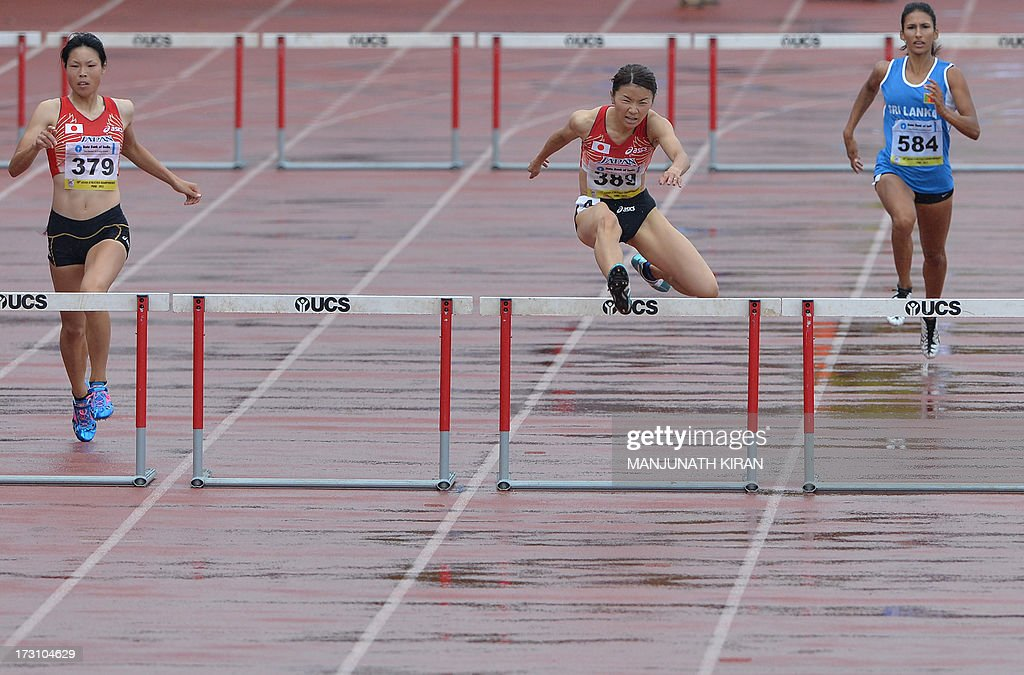 Women's 400 meter hurdles gold medal winner from Japan Satomi Kubokura (C) and compatriot silver medalist Manani Kira (L) jump the last hurdle as they race towards the finish line on the fifth and the final day of the Asian Athletics Championship 2013 at the Chatrapati Shivaji Stadium in Pune on July 7, 2013. AFP PHOTO/Manjunath KIRAN