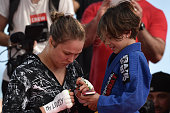 Womens bantamweight champion Ronda Rousey of the United States gives autograph for fan during open training session at Pepe Beach on July 29 2015 in...