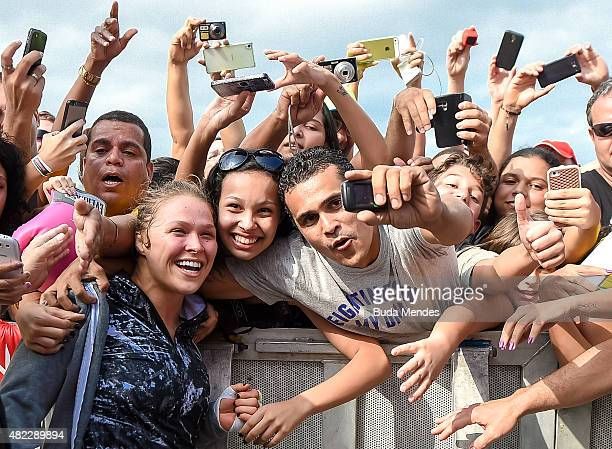 Womens bantamweight champion Ronda Rousey of the United States takes photos with fans during open training session at Pepe Beach on July 29 2015 in...