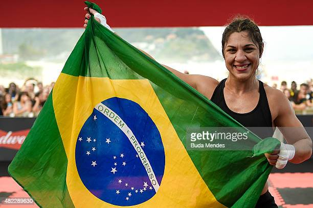 Womens bantamweight contender Bethe Correia of Brazil poses with the flag of Brazil during open training session at Pepe Beach on July 29 2015 in Rio...