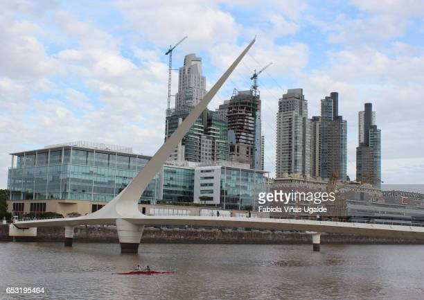 Women's Bridge and luxury buildings behind a river on a cloudy day at Puerto Madero.