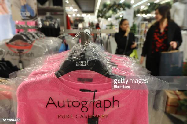 A womens cashmere jumper from the 'Autograph' clothing range hangs in a branded protective plastic cover inside a branch of Marks Spencer Group Plc...