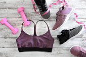 Womens clothes (sport bra), footwear (sneakers) and  equipment (pink dumbbells, tape measure). Active lifestyle concept, Flat lay