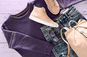 Womens clothing, accessories, footwear (violet sweatshirt, acid washed jeans,  leather backpack and sneakers, sunglasses) on wooden background. Outfit for teens. Top view, flat lay. Trendy colors