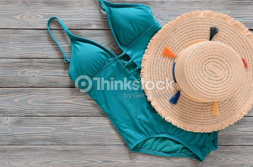 edd71ca6df Womens clothing, accessories (straw hat, blue green swimsuit) on grey wooden  background