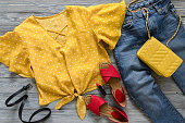 Womens clothing, accessories, shoes (yellow blouse in polka dot, blue jeans, leather red sandals,  yellow crossbody bag, lipstick). Fashion outfit. Shopping concept. Flat lay. Trendy, saturated colors