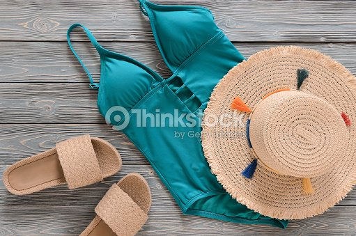 c6ae1e862c Womens clothing, accessories, shoes (straw hat, blue green swimsuit, flip  flops) on grey wooden background. Trendy fashion outfit. Shopping, travel,  summer ...