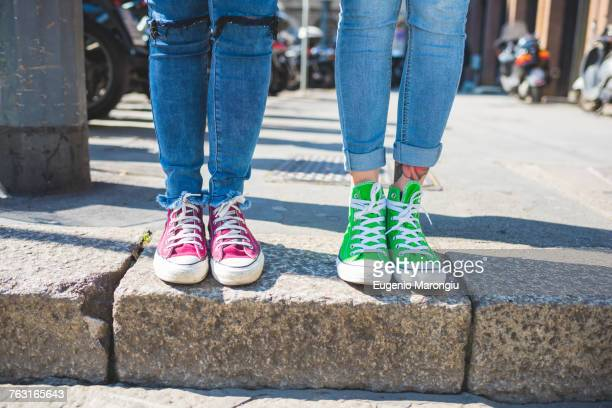 Womens feet in trainers on step, Milan, Italy