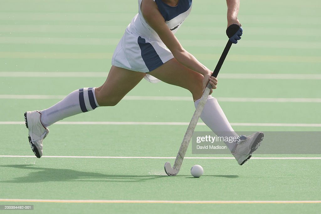 Women's field hockey player in action, low section : Stock Photo