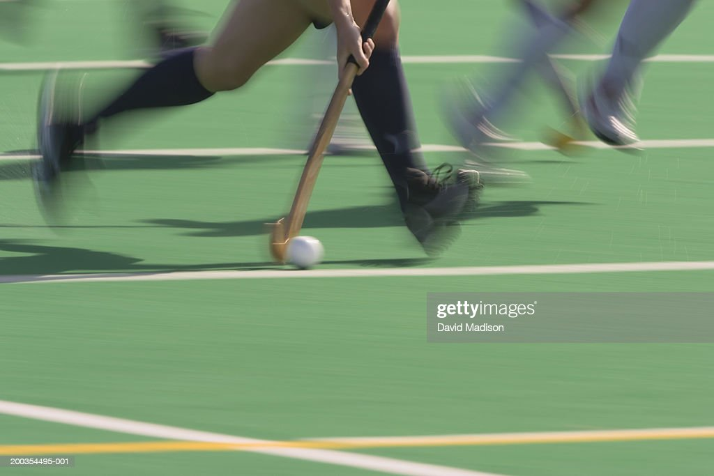 Women's field hockey players in action, low section (blurred motion) : Stock Photo