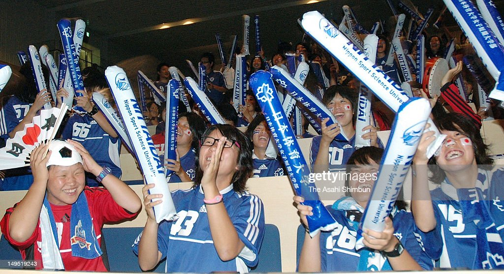Women's football club members of the Nippon Sport Science University cheers while watching the London Olympic women's football match between Japan and Canada on July 26, 2012 in Tokyo, Japan.