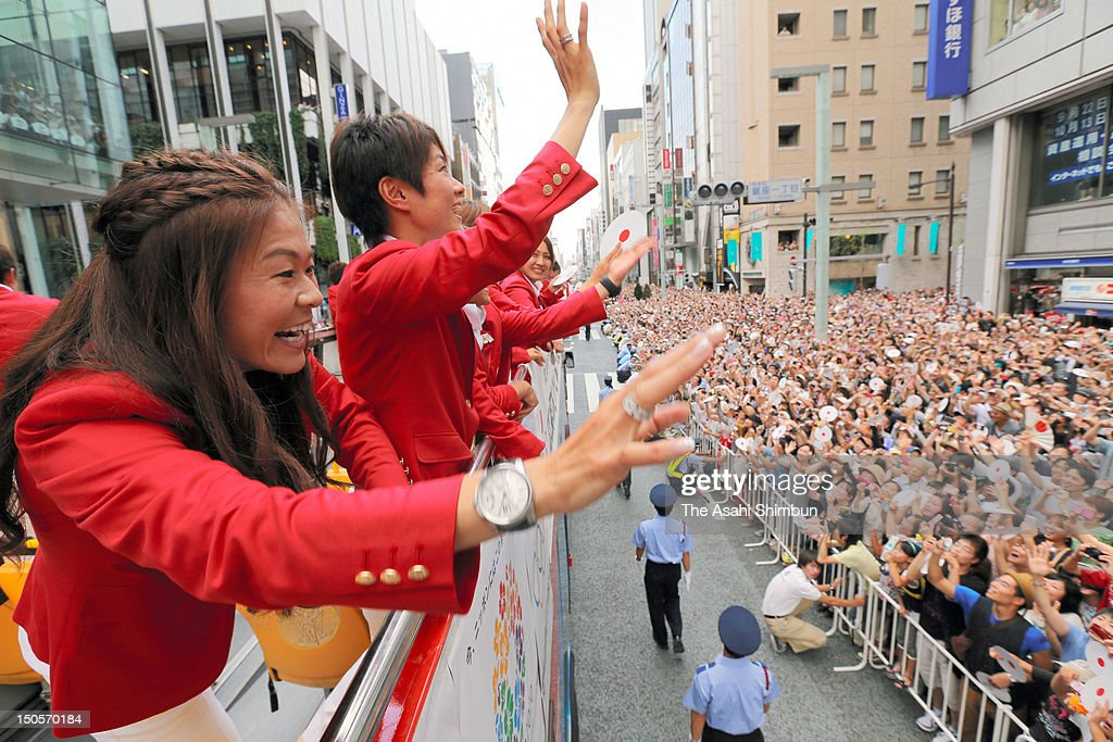 Women's football silver medalists Homare Sawa (L) and Yukari Kinga wave to the crowds from an open-top bus during Japanfs Olympic medalists parade in streets of Ginzaon August 20, 2012 in Tokyo, Japan. An estimated 500,000 people gathered to see the 38 medal winners.
