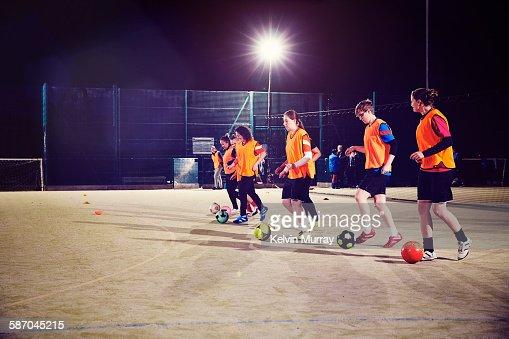 Women's football team run with ball in training