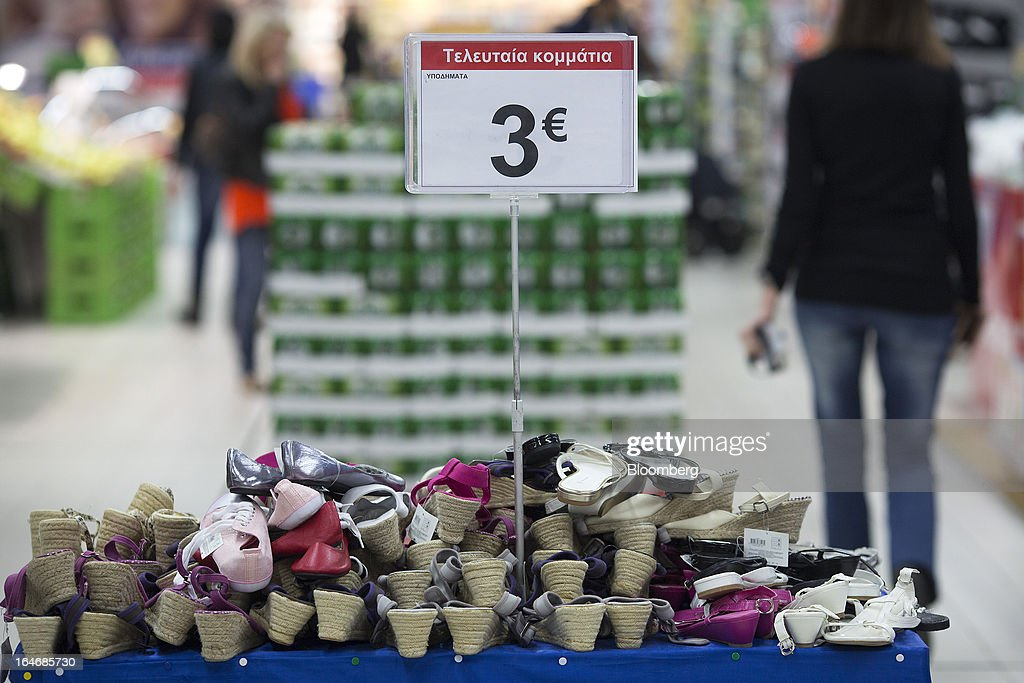 Women's footwear sits on display beneath a three euro sign inside a Carrefour SA supermarket at the Mall of Cyprus in Nicosia, Cyprus, on Tuesday, March 26, 2013. Controls on capital movements to prevent money from draining out of the banking system -- allowed in exceptional circumstances under European Union law -- will remain for 'a matter of weeks,' Cypriot Finance Minister Michael Sarris said. Photographer: Simon Dawson/Bloomberg via Getty Images