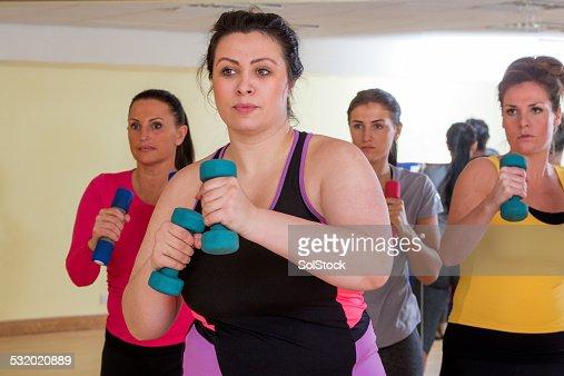 Femme de cours de remise en forme avec poids et haltères