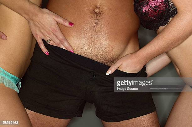 Women's hands in man's boxer shorts