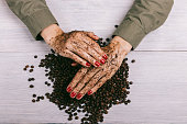 Women's hands with red nail polish applied the coffee scrub, top view