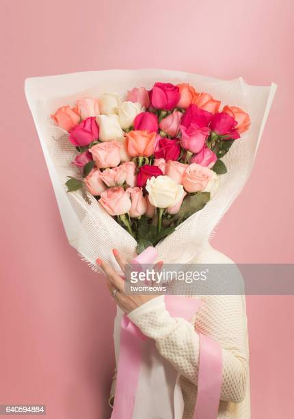 Women's holding a big bouquet of roses on pink background.
