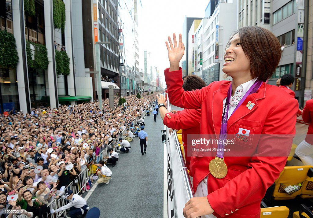 Women's Judo 57kg gold medalist <a gi-track='captionPersonalityLinkClicked' href=/galleries/search?phrase=Kaori+Matsumoto&family=editorial&specificpeople=4919959 ng-click='$event.stopPropagation()'>Kaori Matsumoto</a> waves to the crowds from an open-top bus during Japanfs Olympic medalists parade in streets of Ginzaon August 20, 2012 in Tokyo, Japan. An estimated 500,000 people gathered to see the 38 medal winners.