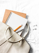 Womens leather handbag, clean blank notepad, pen on a light background, top view. Free space for text