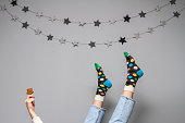 Women's legs in colorful funny socks and jeans on a gray background with the decor of the stars and ginger cookies in the shape of a star in her hand.