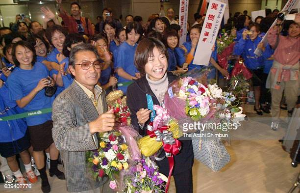 Women's marathon gold medalist Naoko Takahashi and her coach Yoshio Koide pose for photographs on arrival at Narita International Airport on October...