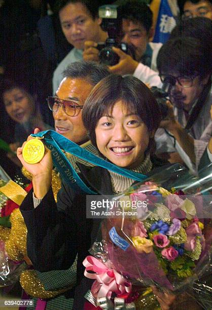 Women's marathon gold medalist Naoko Takahashi poses with her gold medal on arrival at Narita International Airport on October 2 2000 in Narita Chiba...
