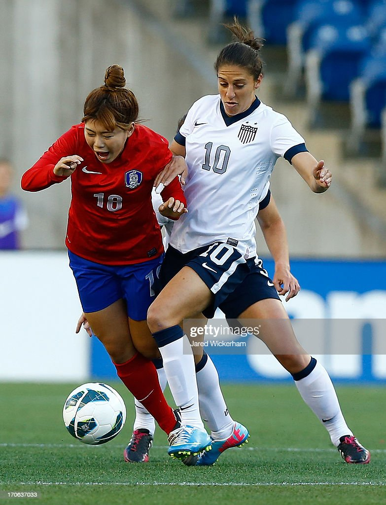 US Womens National midfielder <a gi-track='captionPersonalityLinkClicked' href=/galleries/search?phrase=Carli+Lloyd&family=editorial&specificpeople=736799 ng-click='$event.stopPropagation()'>Carli Lloyd</a> #10 and Korea Republic forward Ji Soyun #10 fight for the ball in the first half during the game at Gillette Stadium on June 15, 2013 in Foxboro, Massachusetts.
