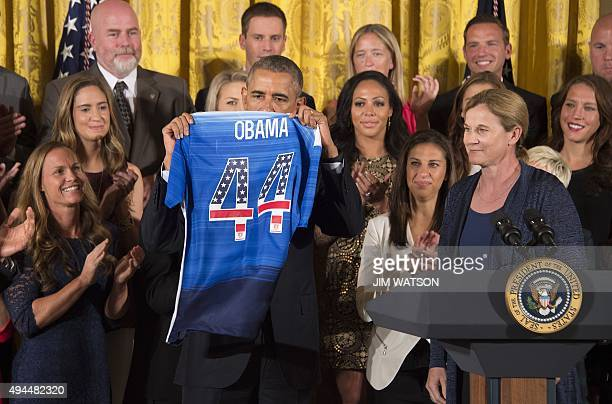 US Women's National Soccer Team's Carli Lloyd and Coach Jill Ellis present US President Barack Obama with a team jersey during an event honoring...