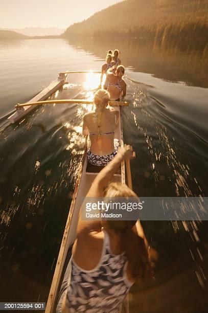 Women's outrigger canoe team paddling canoe on lake, rear view