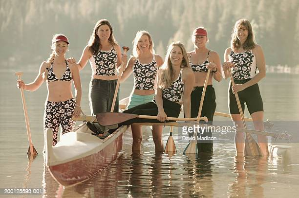 Women's outrigger canoe team standing with canoe in lake, portrait