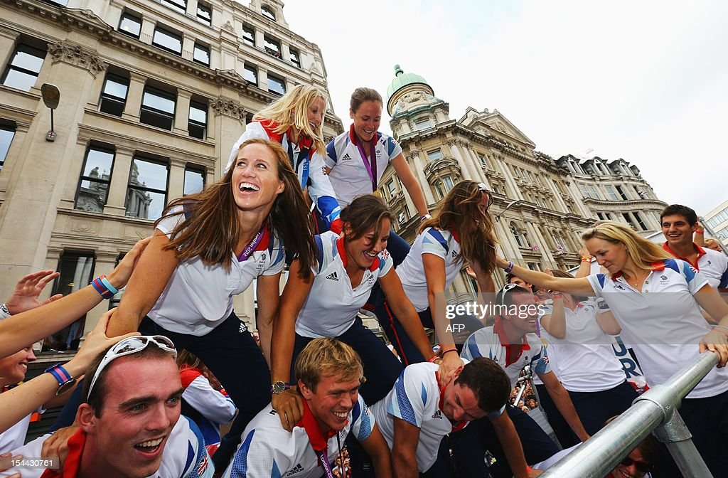 Women's Pair Rowing gold medallist Helen Glover (centre L) and members of the Great Britain rowing team build a human pyramid as they take part in the London 2012 Victory Parade for Team GB and Paralympics GB athletes through central London on September 10, 2012 in London, England. AFP PHOTO/ Paul Gilham )