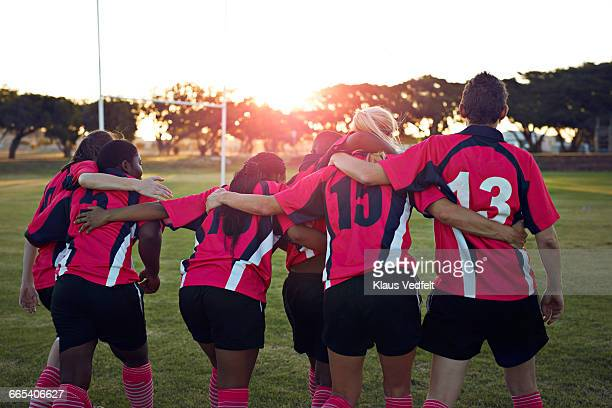 Womens rugby team walking together towards sunset