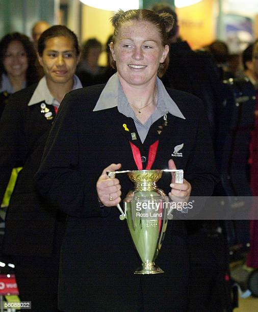 Womens Rugby World Cup winning team member Casey Robertson carries the silver trophy followed by adrianne Lilii and Melodie Robinson after arriving...