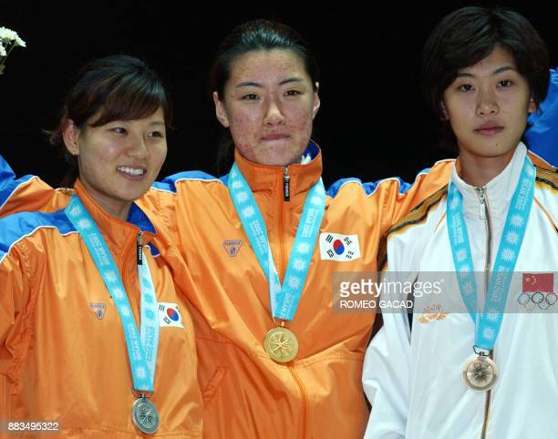 Women's sabre fencing gold medalist Lee Shin Mi of South Korea is flanked silver medalist Lee Gyu Young of South Korea and bronze medalist Tan Xue of...