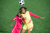 Two women soccer players heading the ball