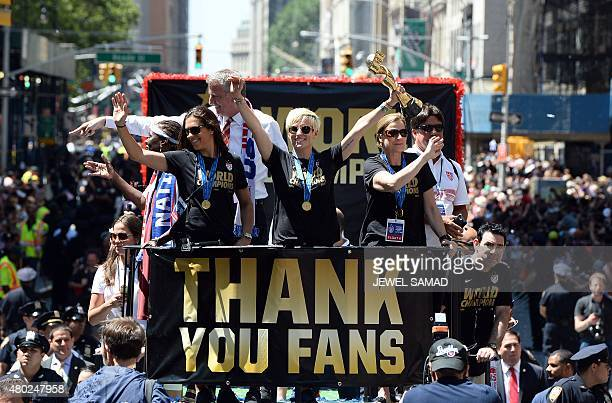 USA women's soccer team midfielder Megan Rapinoe holds up the World Cup 2015 trophy as midfielder Carli Lloyd New York City Mayor Bill de Blasio and...