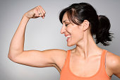 Royalty free stock image of a physically fit young woman flexing her muscles.