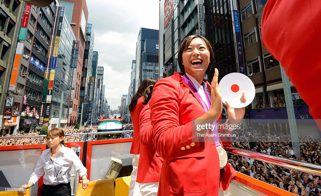 Women's swimming medalist <a gi-track='captionPersonalityLinkClicked' href=/galleries/search?phrase=Satomi+Suzuki&family=editorial&specificpeople=9595153 ng-click='$event.stopPropagation()'>Satomi Suzuki</a> waves to the crowds from an open-top bus during Japanfs Olympic medalists parade in streets of Ginzaon August 20, 2012 in Tokyo, Japan. An estimated 500,000 people gathered to see the 38 medal winners.
