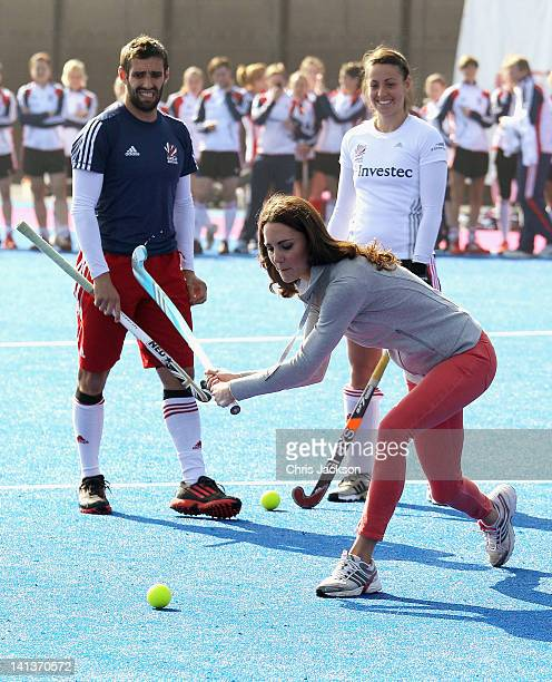 Women's Team GB hockey captain Kate Walsh and men's team player Niall Stott watches Catherine Duchess of Cambridge play hockey with the GB hockey...