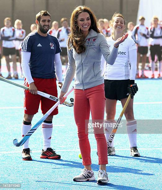 Women's Team GB hockey captain Kate Walsh and men's team player Niall Stott watch as Britain's Catherine Duchess of Cambridge reacts after hitting a...