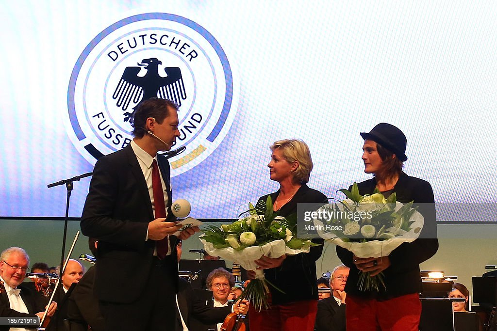 Women's team Germany's head coach Silvia Neid and Women's team Germany's goalkeeper <a gi-track='captionPersonalityLinkClicked' href=/galleries/search?phrase=Nadine+Angerer&family=editorial&specificpeople=2149437 ng-click='$event.stopPropagation()'>Nadine Angerer</a> (l) are honored for the win of the EURO 2013 in Sweden by DFB media director Ralf Koettker(l) on October 24, 2013 in Nuremberg, Germany.