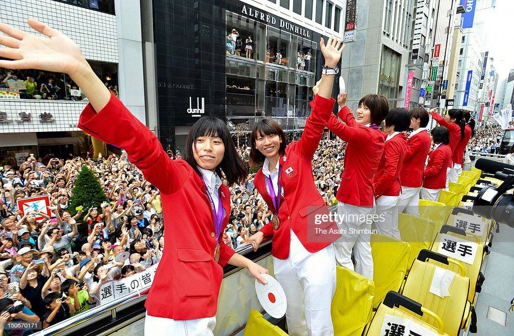Women's volleyball bronze medalists <a gi-track='captionPersonalityLinkClicked' href=/galleries/search?phrase=Risa+Shinnabe&family=editorial&specificpeople=8641931 ng-click='$event.stopPropagation()'>Risa Shinnabe</a> (1L) and <a gi-track='captionPersonalityLinkClicked' href=/galleries/search?phrase=Yukiko+Ebata&family=editorial&specificpeople=7299194 ng-click='$event.stopPropagation()'>Yukiko Ebata</a> (2L) wave to the crowds from an open-top bus during Japanfs Olympic medalists parade in streets of Ginzaon August 20, 2012 in Tokyo, Japan. An estimated 500,000 people gathered to see the 38 medal winners.