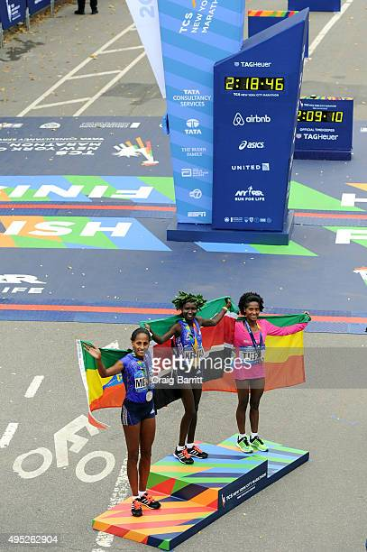 Women's winner Mary Keitany of Kenya poses alongside second place Aselefech Mergia of Ethiopia and third place Tigist Tufa of Ethiopia during the...