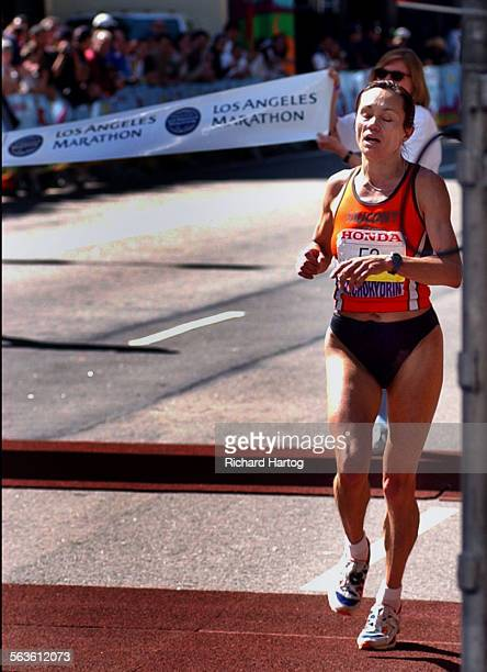 Women's winner Tatyana Pozdnyakova runs around the banner as she crosses the finish line of the LA Marathon Sunday morning in downtown Los Angeles