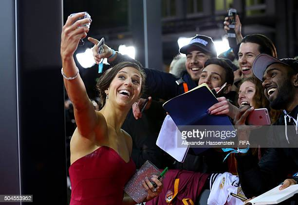 Women's World Player of the Year nominee Carli Lloyd of the United States and Houston Dash takes a selfie with fans as she arrives for the FIFA...